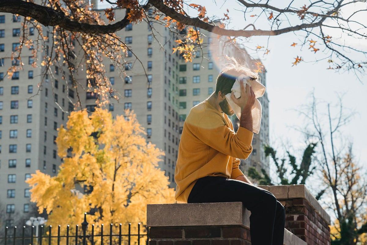 Übermäßiges Schwitzen: Mann wischt sich Schweiß ab